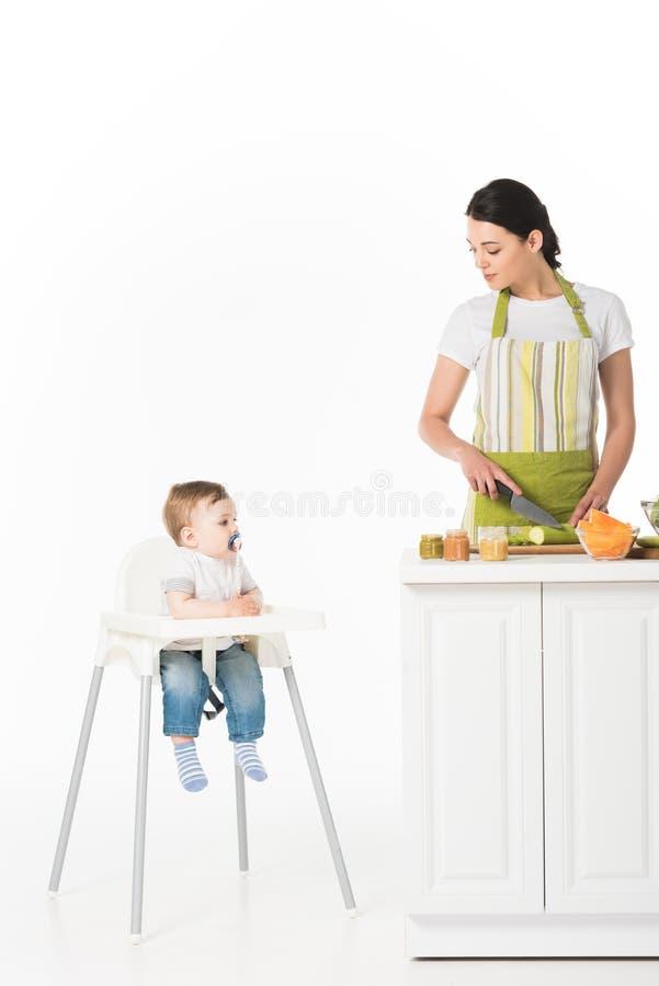 kobieta w fartucha tnącym zucchini i patrzeć małego syna z dziecko pacyfikatoru obsiadaniem zdjęcia stock