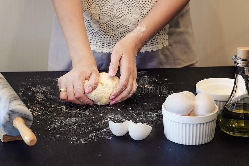 Kobieta w fartuchu ugniata ciasto z jej rękami na czarnym drewnianym stole Składniki dla ciast jajek, jarzynowy olej, mąka Na zdjęcia royalty free