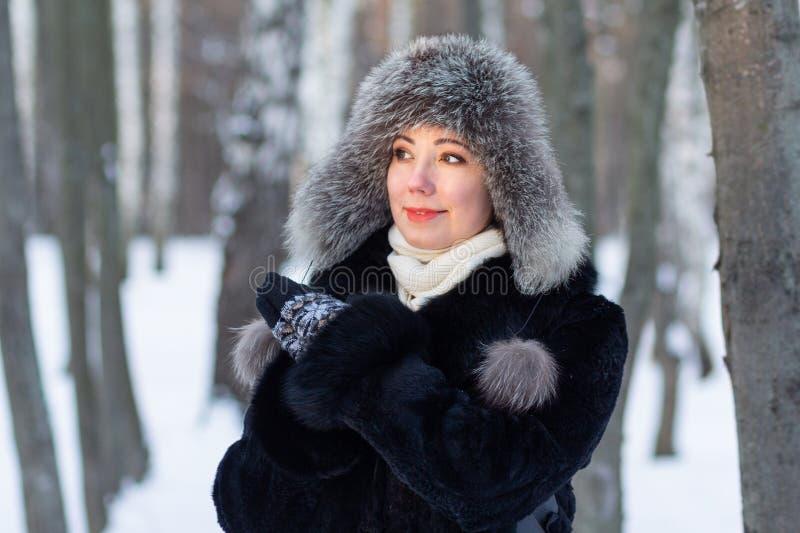 Kobieta w futerkowym kapeluszu w zima parku zdjęcia stock