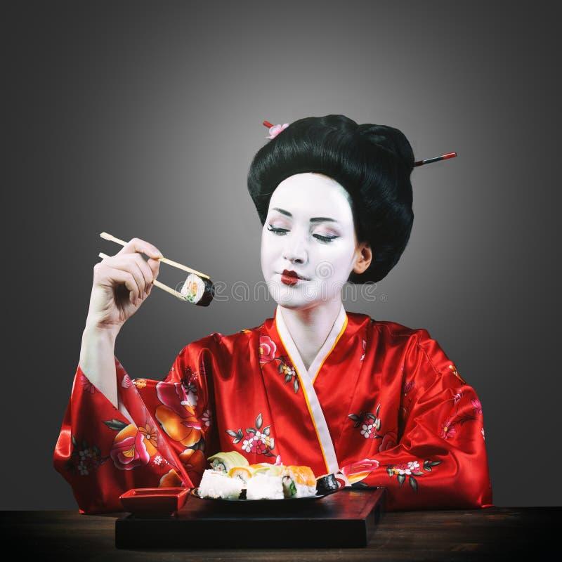 Kobieta w gejszy makeup łasowania suszi zdjęcie royalty free