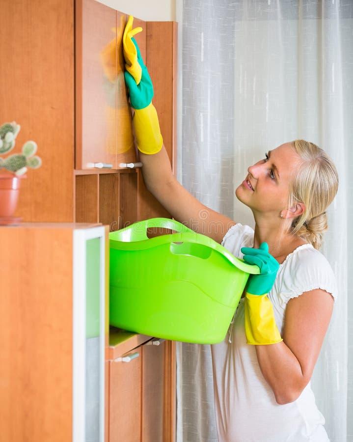 Kobieta w gumowych rękawiczkach czyści indoors obrazy stock