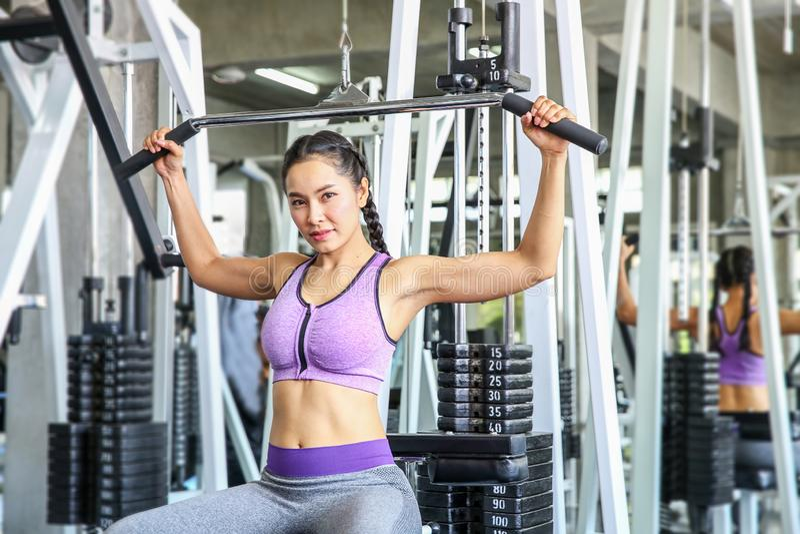 Kobieta w gym sport, sprawność fizyczna, bodybuilding, kobieta ćwiczy mięśnie na maszynie w gym i napina dziewczyna azjatykcia dz zdjęcie royalty free
