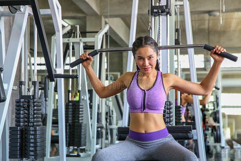 Kobieta w gym sport, sprawność fizyczna, bodybuilding, kobieta ćwiczy mięśnie na maszynie w gym i napina dziewczyna azjatykcia dz obrazy stock