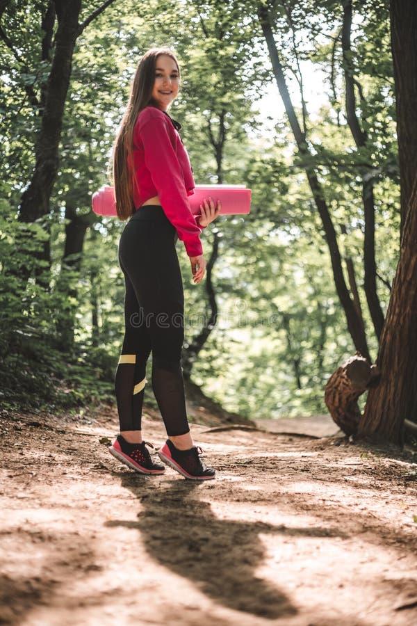 Kobieta w hoodie z sprawności fizycznej matą na trenować outdoors obrazy royalty free