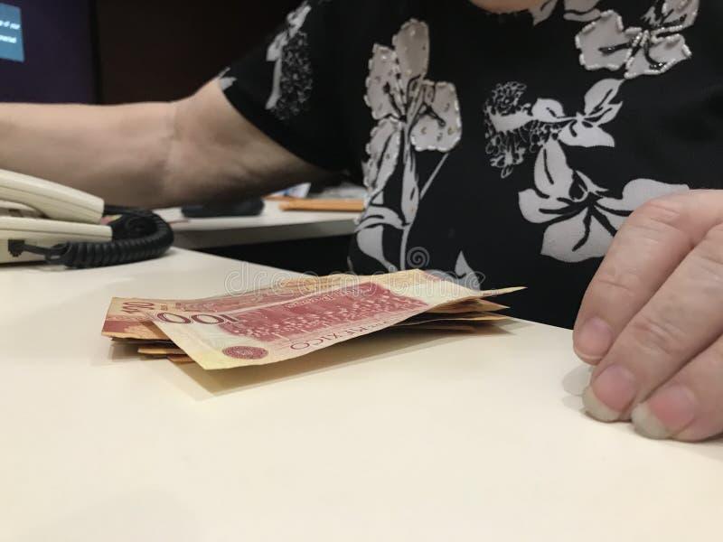 Kobieta w jej biurze z stertą 100 meksykańskiego peso rachunków przed ona zdjęcie royalty free