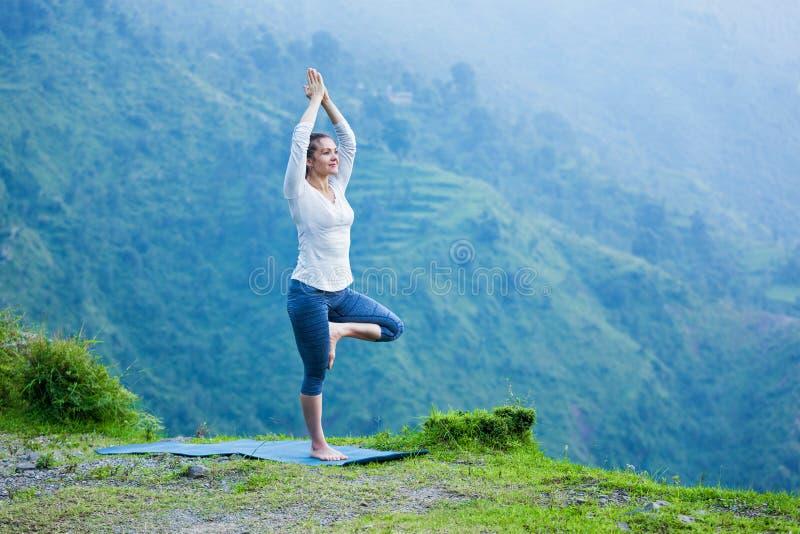 Kobieta w joga asana Vrikshasana drzewnej pozie outdoors obrazy royalty free