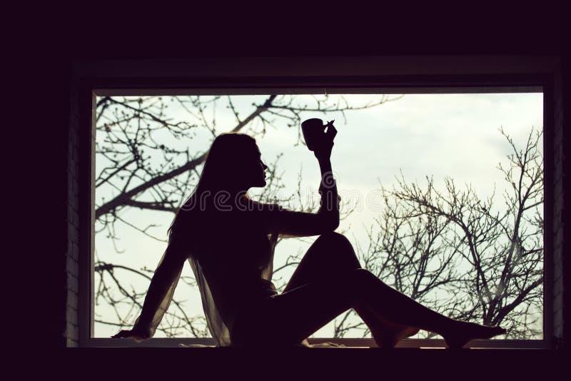 Kobieta w k?a?? przy okno z sukni? zdjęcia stock