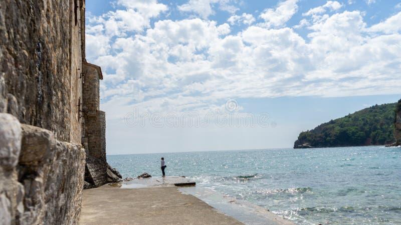 Kobieta w kamiennym porcie w starym miasteczku adriatic morze Woda w rockowym molu i średniowieczny ścienny na zewnątrz fortyfika obraz stock