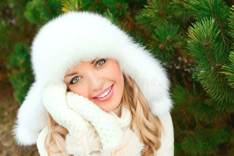 Kobieta w kapeluszu, mitynki, scarves, pulowery, futerko w zimy jodły lesie obraz stock