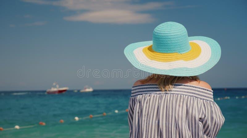 Kobieta w kapeluszu podziwia morze, tylni widok Kobieta na urlopowym pojęciu zdjęcia royalty free