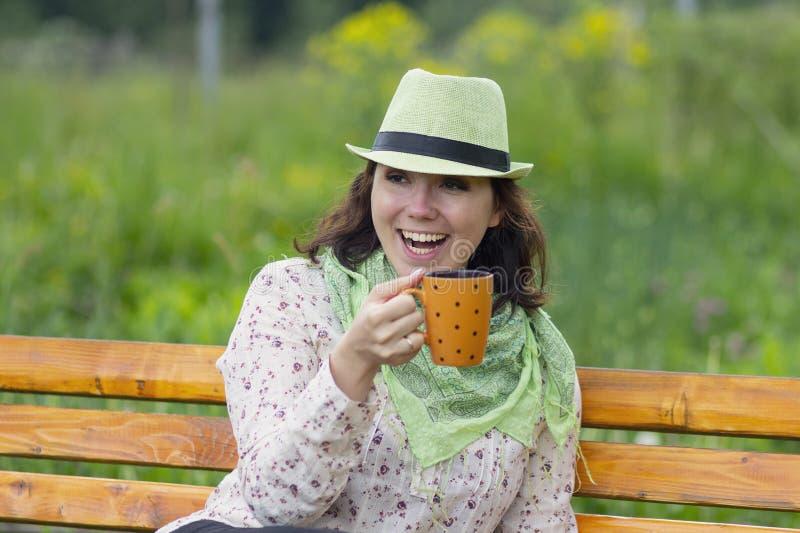 Kobieta w kapeluszu z kubkiem podczas odpoczynku i fotografia stock