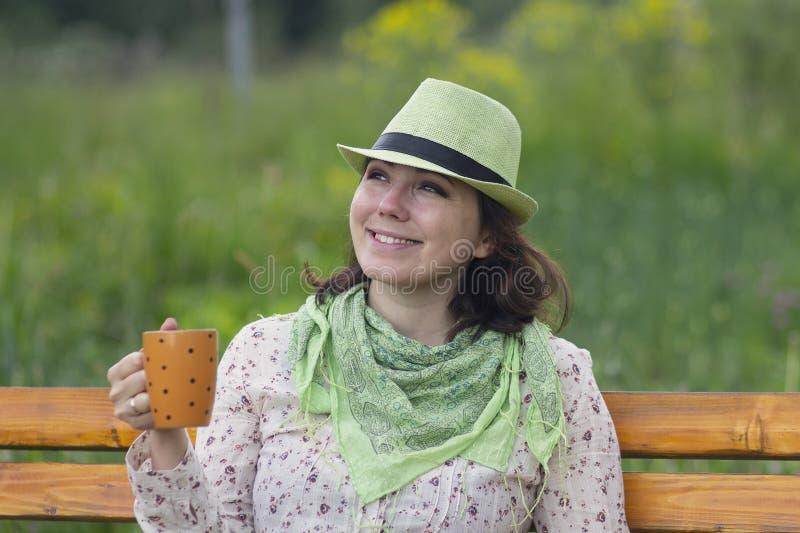 Kobieta w kapeluszu z kubkiem podczas odpoczynku i obrazy stock