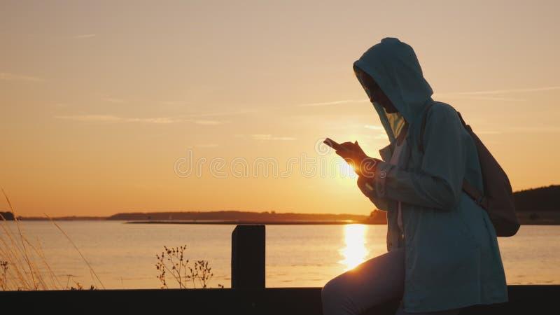 Kobieta w kapiszonie siedzi na ogrodzeniu blisko malowniczego jeziora, używa smartphone piękny zachód słońca zdjęcia stock