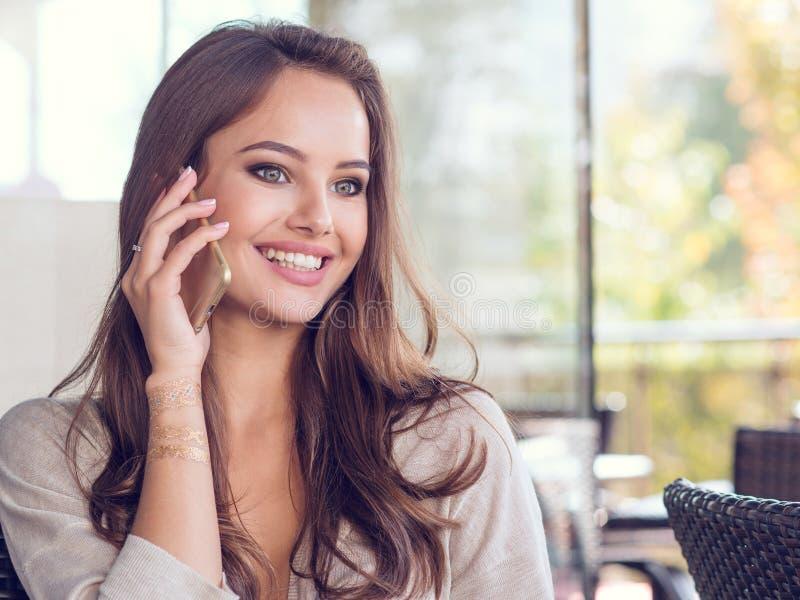 Kobieta w kawiarni pić kawowy i używać jej telefon komórkowego obraz stock
