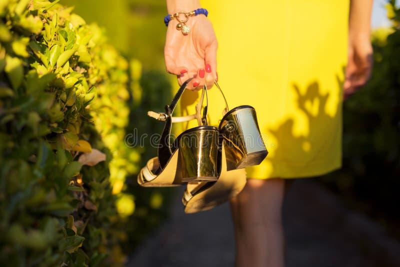Kobieta w kolor żółty sukni mienia szpilek butach w ręce fotografia stock