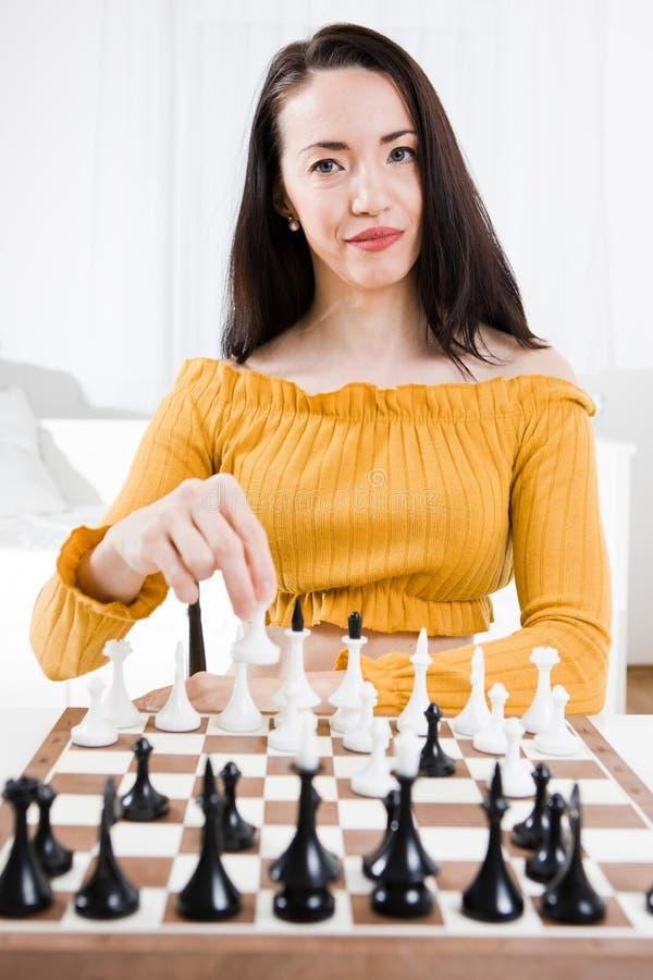 Kobieta w kolor żółty sukni obsiadaniu przed szachy - twój ruch obrazy stock
