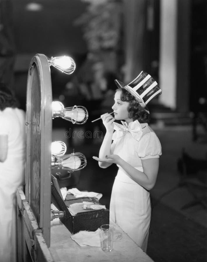 Kobieta w kostiumu stosuje makeup zdjęcie royalty free