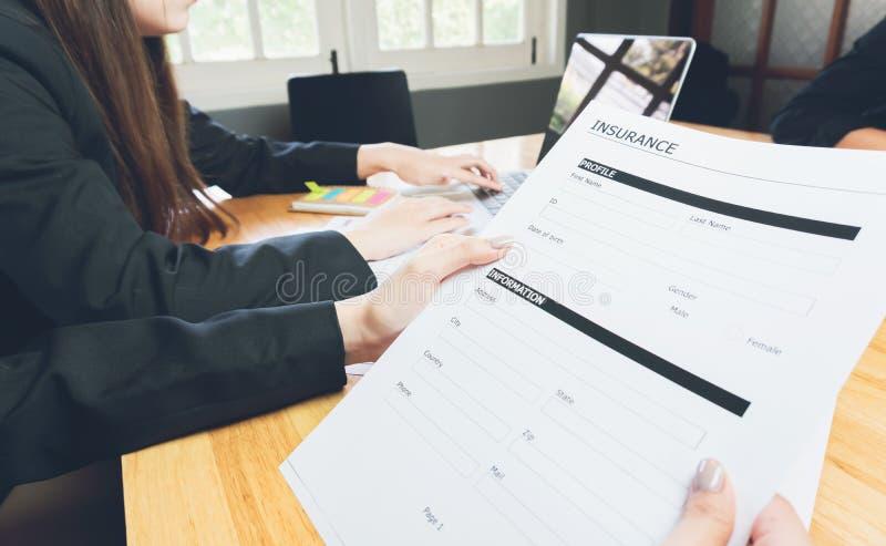 Kobieta w kostiumu w biurze pokazuje polisę ubezpieczeniową, pojęcie pełnia ich laptop dostawać online fotografia royalty free