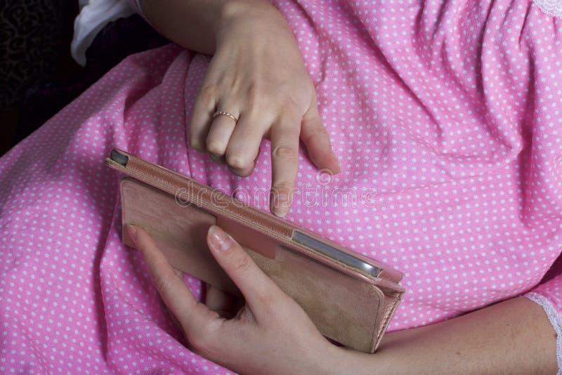 Kobieta w koszula nocnej pracuje z pastylką podczas gdy kłamający w łóżku Dotyka ekran z ona palce obraz royalty free