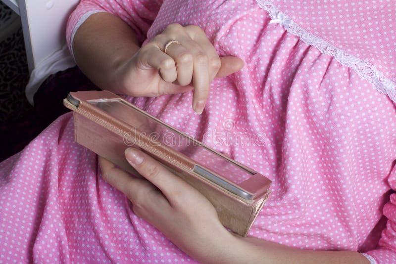Kobieta w koszula nocnej pracuje z pastylką podczas gdy kłamający w łóżku Dotyka ekran z ona palce zdjęcie stock