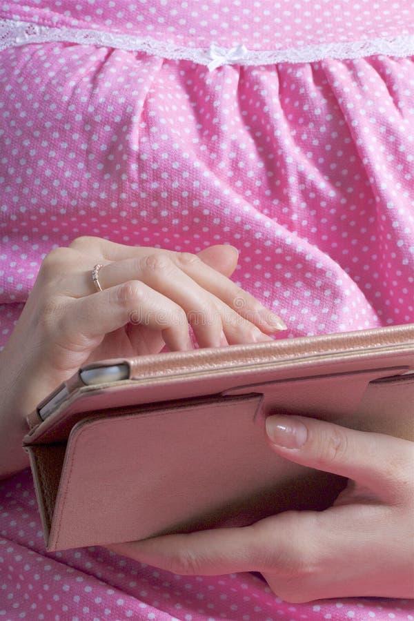 Kobieta w koszula nocnej pracuje z pastylką podczas gdy kłamający w łóżku Dotyka ekran z ona palce fotografia royalty free