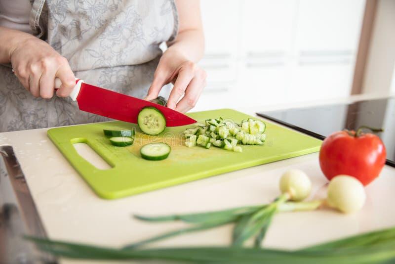 Kobieta w kuchennym fartuchu ciie ogórek na tnącej desce z czerwonym nożem obraz stock