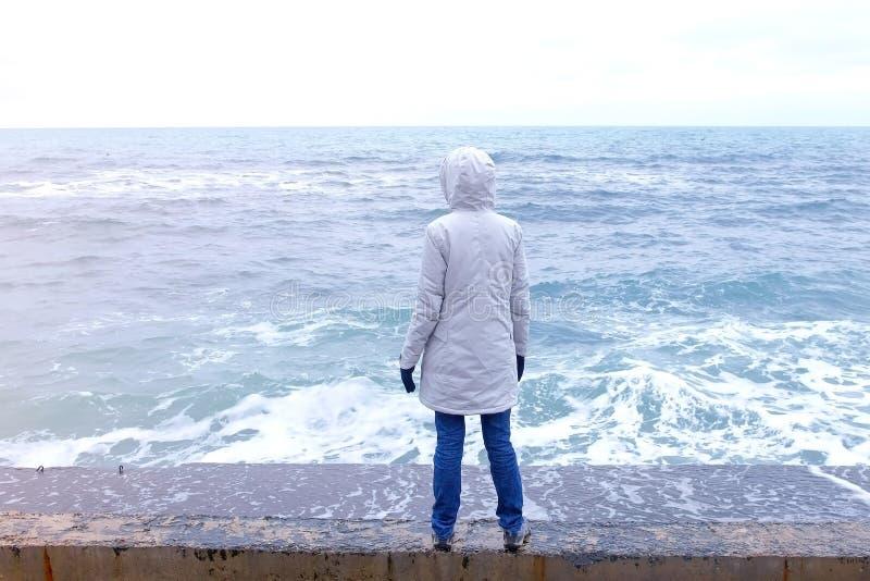 Kobieta w kurtki białych stojakach na nabrzeżu na plaż spojrzeniach przy burzą macha widok z powrotem fotografia stock