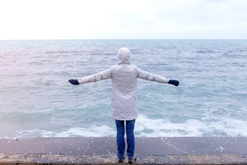 Kobieta w kurtki białych stojakach na nabrzeżu na plaży zbroi szeroko rozpościerać i spojrzenia przy burz falami widok z powrotem zdjęcia royalty free