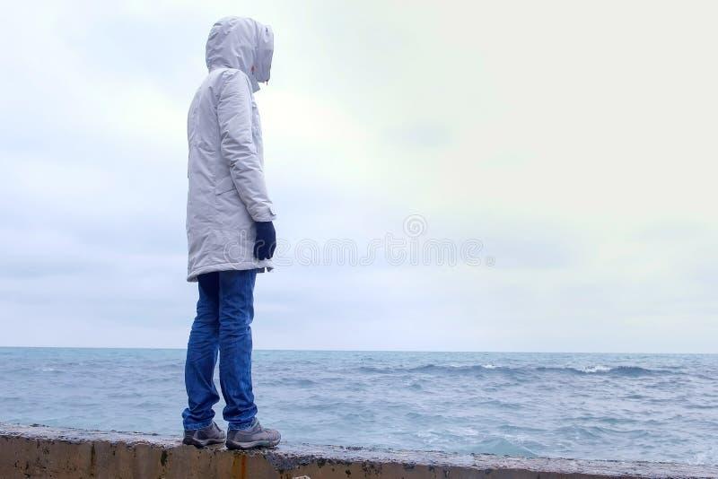 Kobieta w kurtki białych stojakach na nabrzeżu na plaży i spojrzeniach przy burz falami Boczny widok obrazy stock