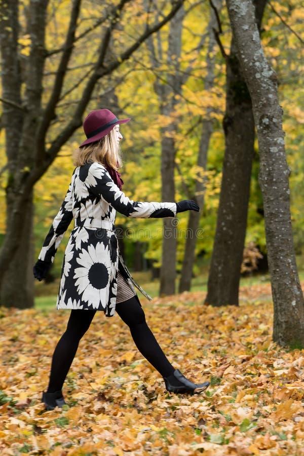 Kobieta w kwiecistym wzorzystości wina i żakieta czerwieni kapeluszu w parku rzeką, Szczęśliwa dziewczyna, kolorowej jesieni laso obrazy royalty free