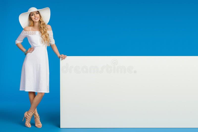 Kobieta W lato sukni, słońce kapeluszu I szpilkach, Pozuje Z Białym sztandarem fotografia stock