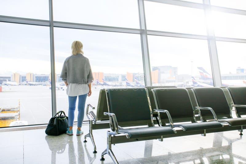 Kobieta w lotnisku, patrzeje przez okno przy samolotami zdjęcia royalty free