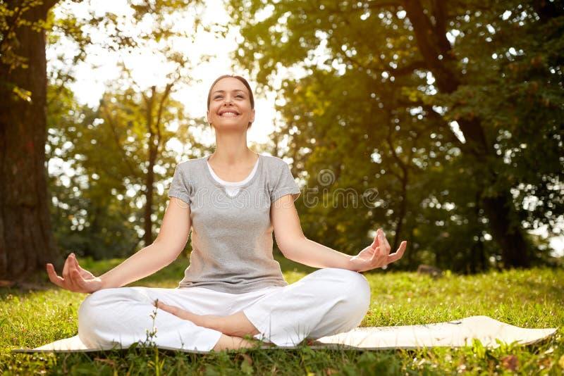 Kobieta w lotos pozie medytuje w zieleń parku obrazy royalty free