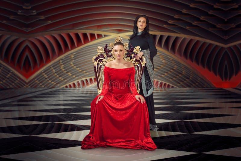 Kobieta w luksusowym togi sukni obsiadaniu na kr?lowej ` s tronie obrazy royalty free