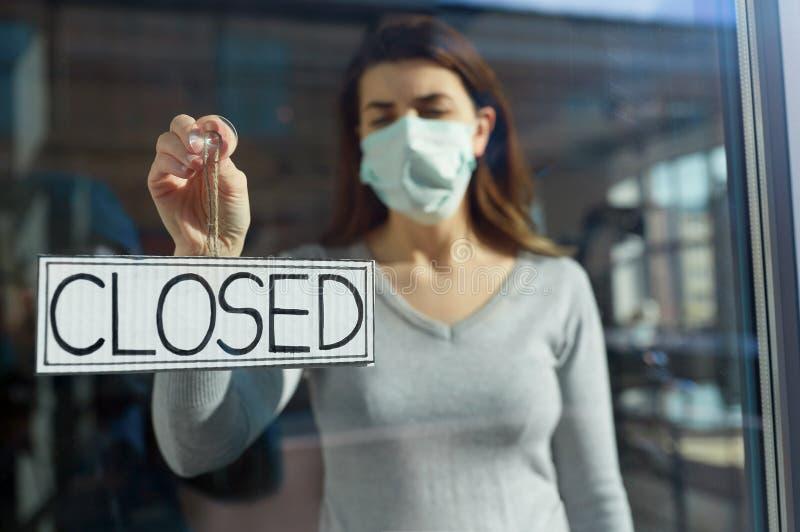 Kobieta w masce wisząca baner zamknięta na drzwiach obraz stock