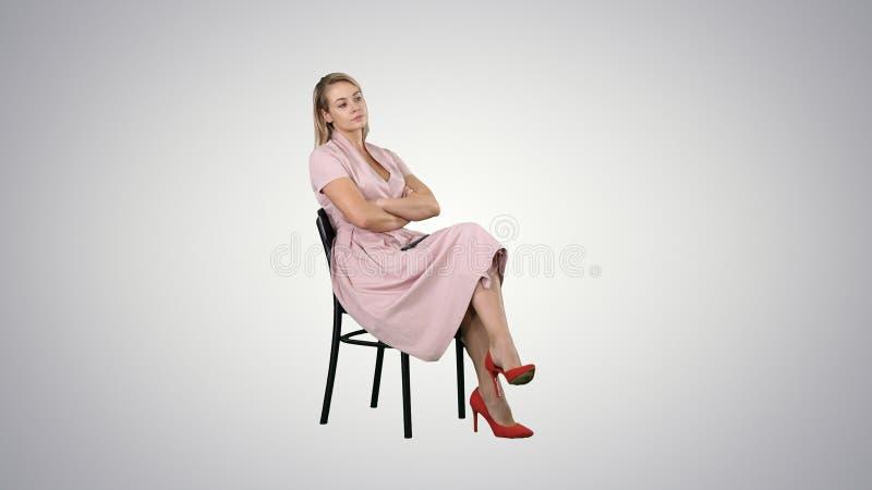 Kobieta w menchiach ubiera obsiadanie na krześle czekać na someone na gradientowym tle obrazy stock