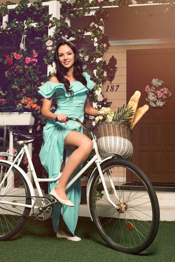 Kobieta w mennicy sukni pozyci z rowerowy pobliskim jej dom zdjęcia stock
