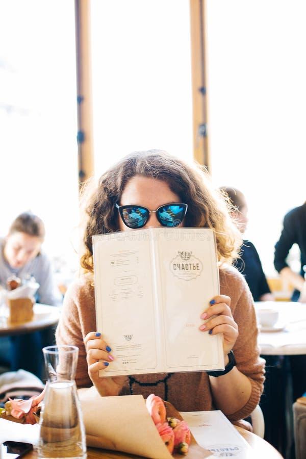 Kobieta w menu trzymania okularów przeciwsłonecznych fotografia stock