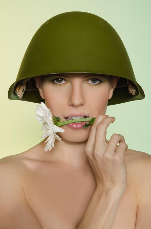 Kobieta w militarnym hełmie z chamomile usta fotografia royalty free