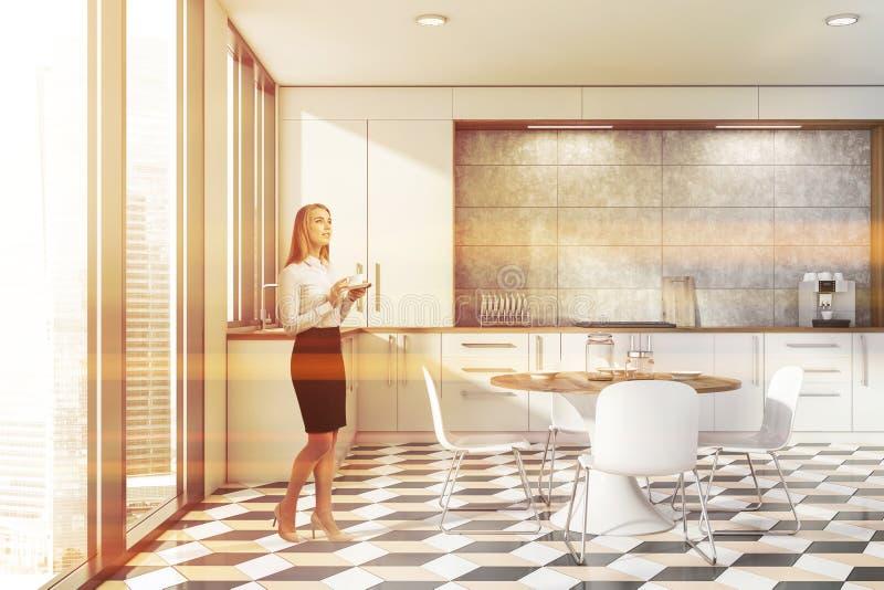 Kobieta w minimalista dachówkowej i białej kuchni zdjęcie royalty free