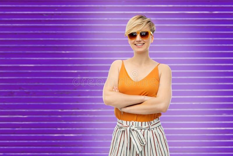 Kobieta w okularach przeciwsłonecznych nad ultrafioletowym tłem zdjęcia stock