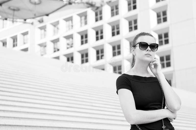 Kobieta w okularach przeciwsłonecznych pozuje na schodkach i buduje w Francja zdjęcie stock