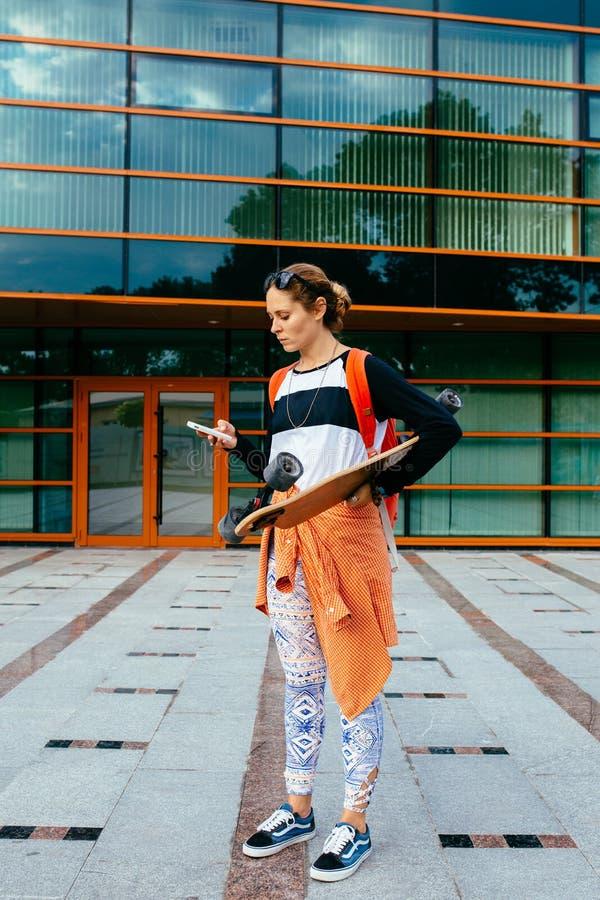 Kobieta w okularach przeciwsłonecznych z longboard i pomarańcze koszula wysyła wiadomość tekstową od jej telefonu komórkowego Kob zdjęcia stock