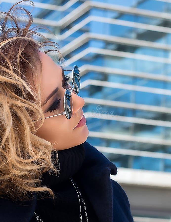 Kobieta w okularach przeciwsłonecznych z odbiciem robić szkło budynek zdjęcia stock
