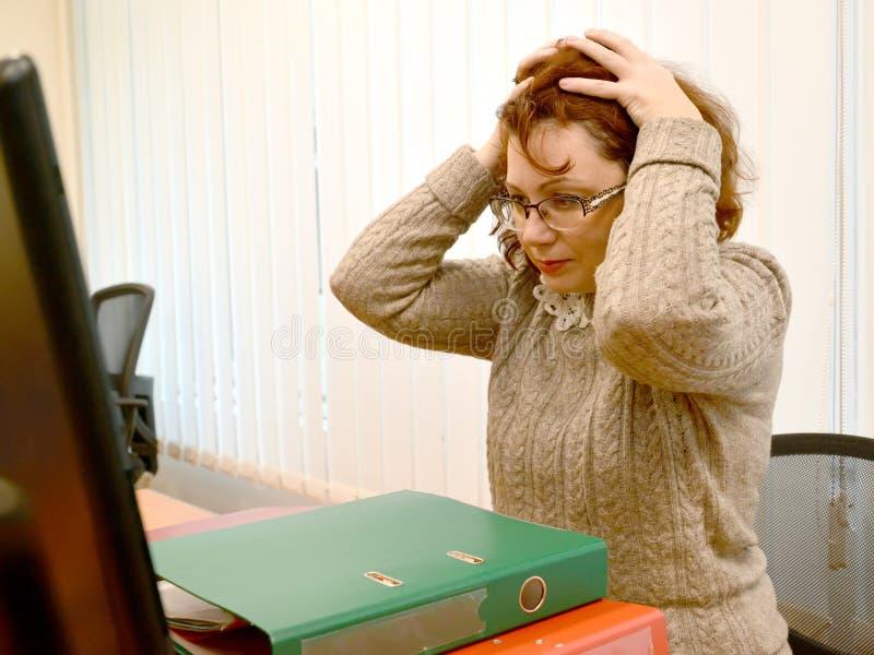Kobieta w panice spinał z rękami głowę, patrzeje w monitorze obrazy stock