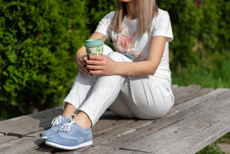 Kobieta w pasiastych spodniach, błękitnych sneakers i t koszulowy obsiadanie na mienia odpoczywać, ławce i filiżanka kawy i zdjęcia stock