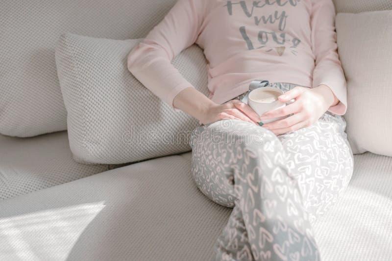 Kobieta w pj ` s na łóżku w trzymać filiżankę kawy zdjęcie stock