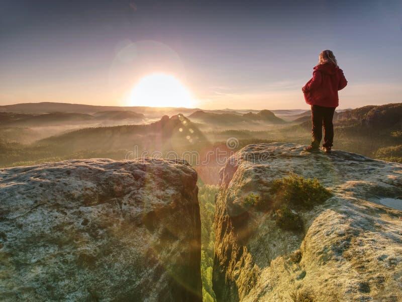 Kobieta w plenerowych ubraniach cieszy się widok przy szczytem w górach zdjęcie royalty free