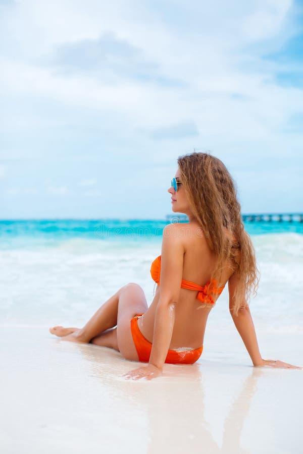 Kobieta w pomarańczowym bikini na tropikalnej plaży obraz royalty free