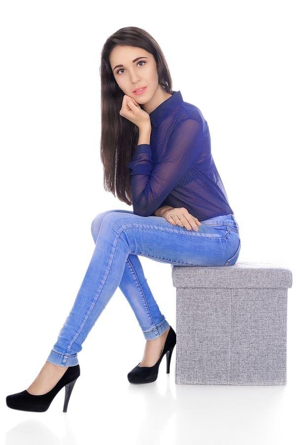 Kobieta w przejrzystej koszula, cajgach i piętach, siedzi na krześle obraz royalty free